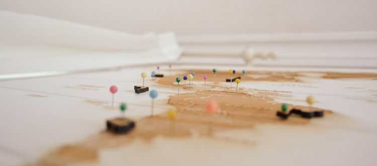 Flat view of a map with colored pushpins in it.